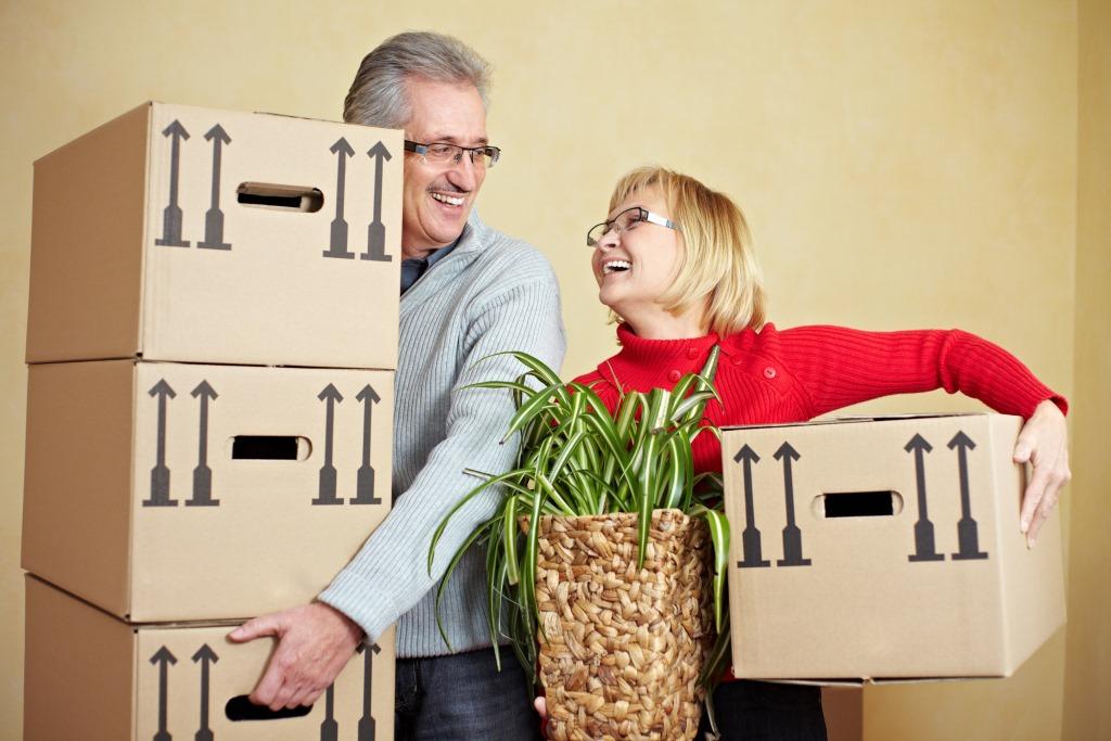 Lachendes Paar mit Umzugskartons
